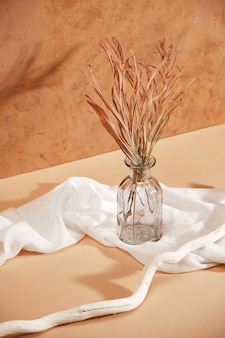 Minimalistic composition of dried grass in glass vase as home decoration fabric and a white tree