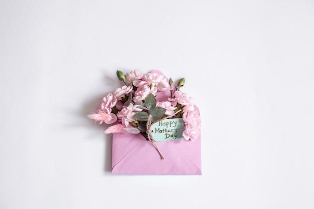 母の日のミニマルな構成。コピースペース内に花が飾られた装飾的な封筒。