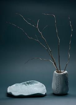 陶土の手作り花瓶とお皿に生け花をあしらった、和風のミニマルな構図。縦ショット