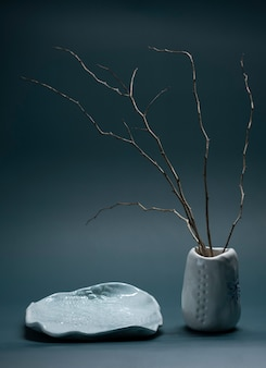 Minimalistic composition in japanese asian style with ikebana in an earthenware clay handmade vase and plate. vertical shot