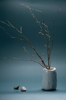 Minimalistic composition in japanese asian style with ikebana in an earthenware clay handmade vase and stones. vertical shot