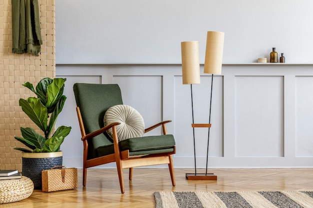 Minimalistic composition at living room interior with design green armchair, beige panel, plants, cube, shelf, copy space, decoration and elegant personal accessories in stylish home decor.
