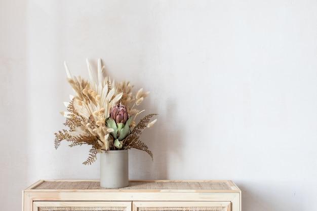 Минималистичная композиция из сухих цветов в керамической цилиндрической вазе в качестве украшения для дома.