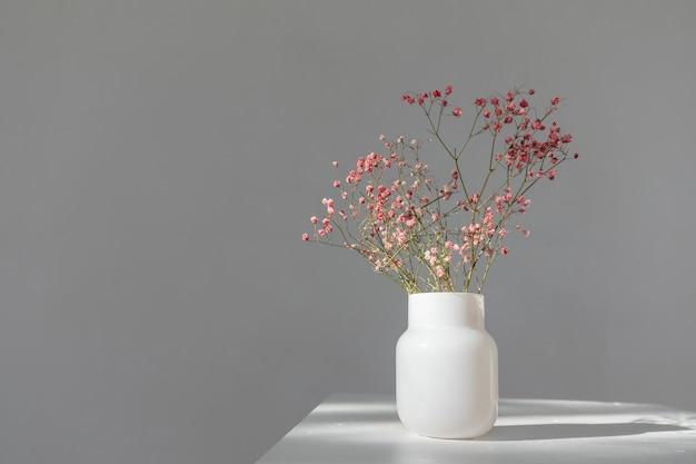 흰색 배경에 가면 아래 원통형 유리 꽃병에 말린 분홍색 꽃의 최소한의 구성