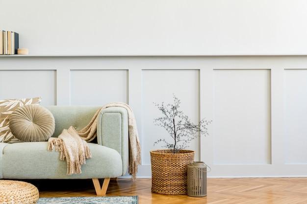 디자인 소파, 커피 테이블, 식물, 책, 장식, 베개, 격자 무늬, 카펫, 목재 패널 및 세련된 가정 장식의 우아한 개인 액세서리가있는 거실의 미니멀리즘 구성.