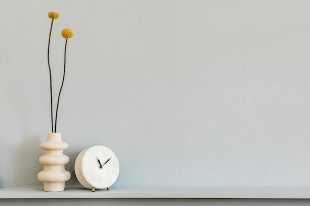 Минималистичная композиция на полке с засушенным цветком в дизайнерской вазе и белыми часами. серая стена. скопируйте пространство.