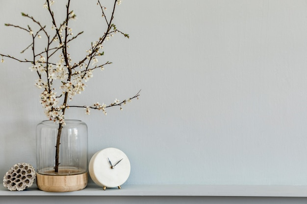 Минималистичная композиция на полке с сухоцветом в дизайнерской вазе, белыми часами и украшением стильного интерьера гостиной. серая стена. скопируйте пространство.