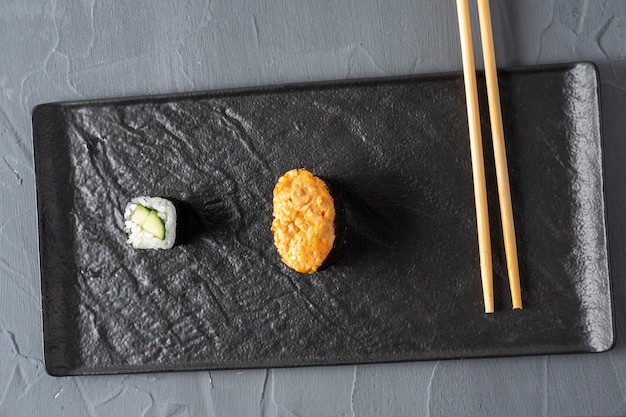 Minimalistic composition. roll, gunkan and bamboo sticks on a textured dark plate. top view, flat lay