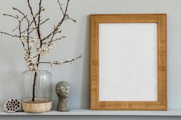 茶色のモックアップフォトフレーム、花瓶の枯れた花、彫刻、スタイリッシュな家のインテリアのエレガントなパーソナルアクセサリーを備えた棚のミニマルなコンセプト。