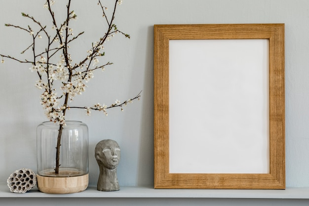 Minimalistic concept on the shelf with brown mock up photo frame, dired flower in vase, sculpture and elegant personal accessories at stylish home interior.