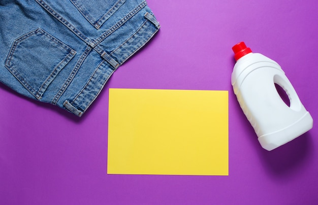 Minimalistic concept of washing. paper for copy space, jeans, bottle of washing gel on purple table. top view