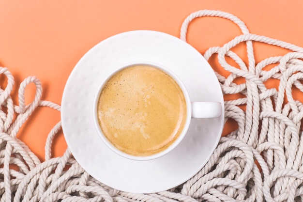 Minimalistic cotton white rope background with cup of cappuccino on a coral colored background.