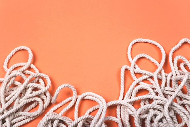 Minimalistic cotton white rope background with texture and contrast on bright coral background.