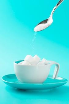 砂糖の立方体とスプーンでミニマルなカップ