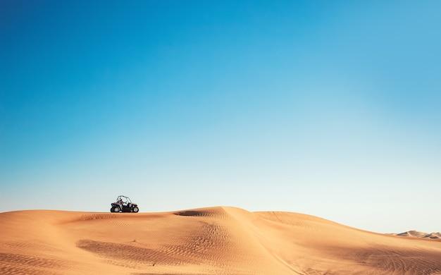 하늘, 모래 언덕, 버기 쿼드 바이크 한 대가 있는 최소한의 사막 전망