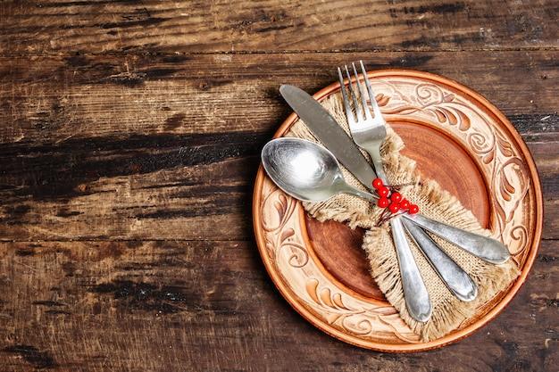 ミニマルなディナーテーブル。カトラリー、荒布ナプキン、お祭りの装飾が施された国民の祝日の素朴なコンセプト。ヴィンテージ木製テーブル、上面図