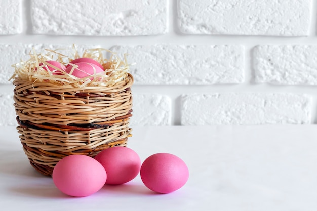 籐のバスケットと白い背景の上のピンク色の卵とミニマルなイースターの構成。コピースペース