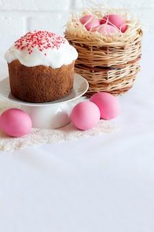 ピンク色の卵と白い背景の上のイースターケーキと籐のバスケットとミニマルなイースターの構成。コピースペース