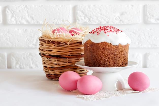 ピンク色の卵と白い背景の上のイースターケーキと籐のバスケットとミニマルなイースターの構成