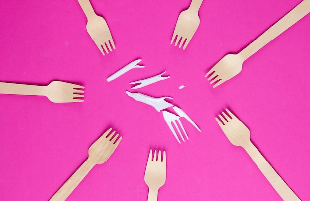 Minimalistic ecologically clean still life. pop art. broken plastic fork among many wooden forks on pink background. cutlery made from natural materials