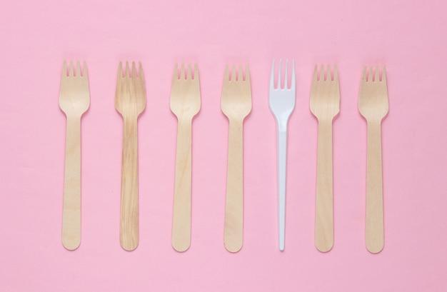 Минималистичная экологическая концепция. деревянные и пластиковые вилки на розовом пастельном фоне. творческий экологический фон