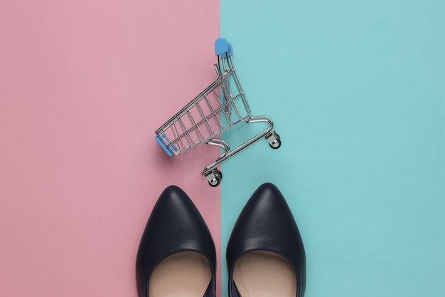 ミニマルなファッションとショッピングのコンセプトブルーピンクのパステルカラーの背景に革のハイヒールの靴のショッピングトロリー