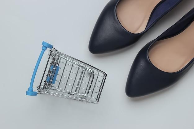 ミニマルなファッションとショッピングのコンセプト白い背景の上の革のハイヒールの靴のショッピングトロリー