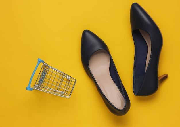 ミニマルなファッションとショッピングのコンセプト黄色のパステルカラーの背景に革のハイヒールの靴のショッピングトロリー