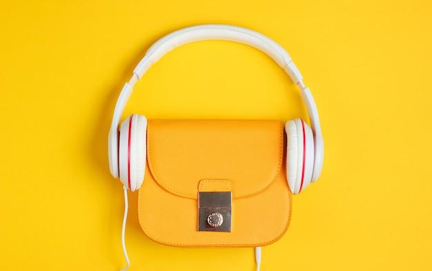 미니멀리즘 패션 컨셉. 노란색 배경에 헤드폰 유행 노란색 가죽 가방. 평면도