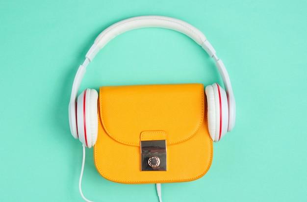 미니멀리즘 패션 컨셉. 파란색 배경에 헤드폰 유행 노란색 가죽 가방. 평면도