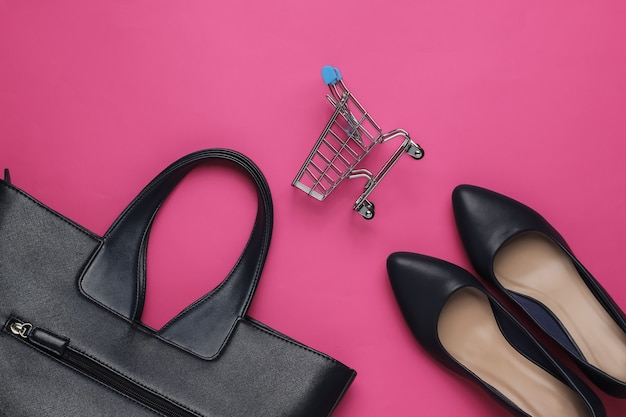 Minimalistic fashion and shopping concept leather high heel shoes shopping trolley bag on pink background