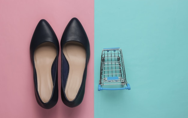 Minimalistic fashion and shopping concept leather high heel shoes shopping trolley on a bluepink pastel background