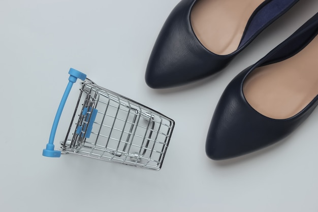 Minimalistic fashion and shopping concept leather high heel shoes shopping trolley on white background