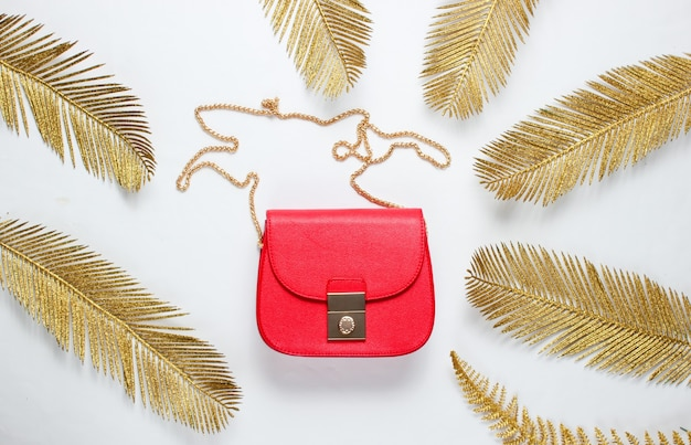 Minimalistic fashion still life. leather red bag among decorative golden palm leaves on white background. top view