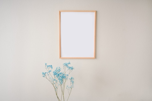Minimalistic female still life art scene pastel colors. empty picture poster mock up frame on beige wall, stylish composition with blue dry flowers