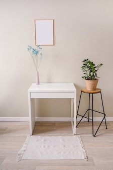 Minimalistic female still life workplace interior pastel colors. white table, empty poster mock up frame, stylish pink powder vase with blue dry flowers