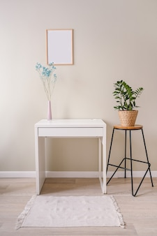 Minimalistic female still life workplace interior pastel colors. white table, empty poster mock up frame, stylish pink powder vase with blue dry flowers Premium Photo