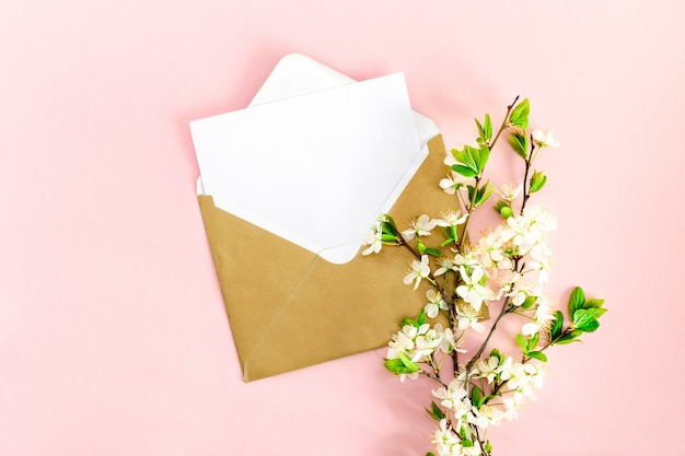 A minimalistic flat lay composition with a mock-up of a white blank postcard for text, an envelope from craft paper, a pen, a branch of blooming cherry with flowers on a pink background. top view.