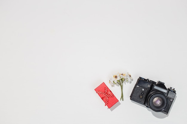 Minimalistic flat lay composition with retro camera, red gift box and spring field flower on white background.