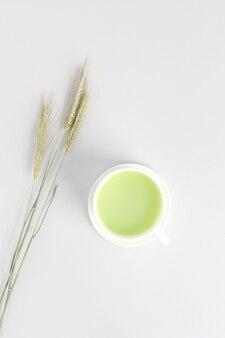 Minimalistic flat lay with cup of green matcha tea and three wheel of rye