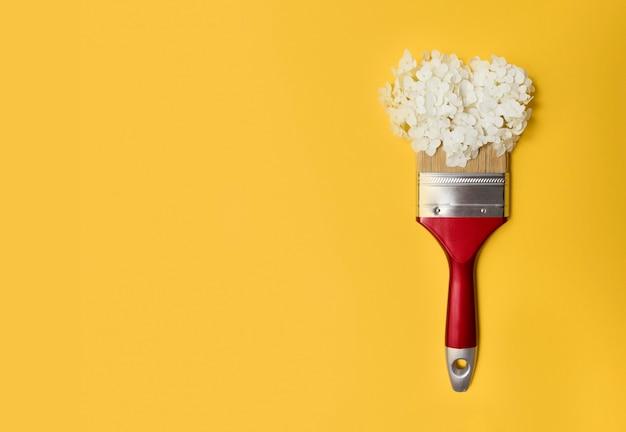 노란색 빈 배경에 브러시와 흰색 수국 꽃의 최소한의 꽃 개념. 최소한의 자연 플랫 레이, 평면도, 복사 공간, 꽃 구성. 배너.