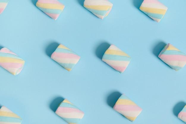 広告用のコピースペースと色の青いパステルカラーの背景に配置されたパターンのカラフルな甘いマシュマロの背景のミニマルな食品組成