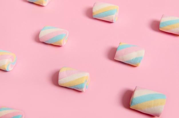 広告用のコピースペースとピンクのパステルカラーの背景に配置されたパターンのカラフルな甘いマシュマロの背景のミニマルな食品構成