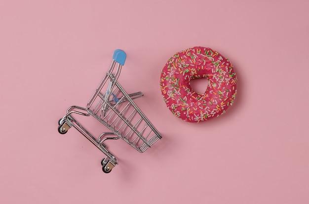 Минималистичный пищевой натюрморт. застекленный пончик и тележка для покупок на розовом пастельном фоне. сладкий десерт. тенденция ванильного цвета. вид сверху