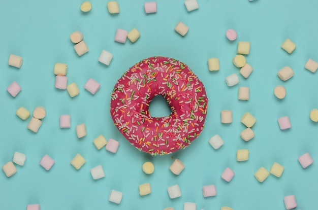 Минималистичный пищевой натюрморт. глазированный пончик с зефиром на голубом пастельном фоне. тенденция ванильного цвета. поп-арт