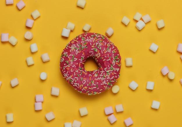 Минималистичный пищевой натюрморт. глазированный пончик с зефиром на желтом фоне. вид сверху