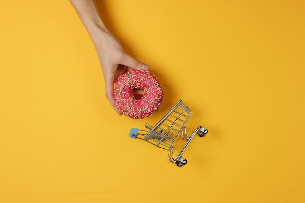 Minimalistic food still life. hand holding pink glazed donut and shopping trolley on yellow background.  sweet dessert. top view