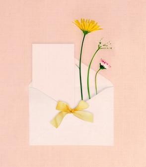 デザインのためのスペースのある封筒に花が付いたミニマルなグリーティングカード