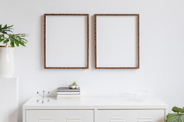 本、スタイリッシュなポットの美しい植物、ホームアクセサリーが付いた白い棚に2つの茶色の木製モックアップフォトフレームを備えたインテリアのミニマルな家の装飾。白い壁。