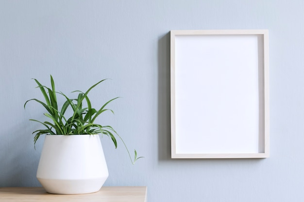 Minimalistic home interior with photo frame on the brown table with plant